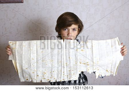 preteen handsome boy with armenian lavash sheet in hands close up photo