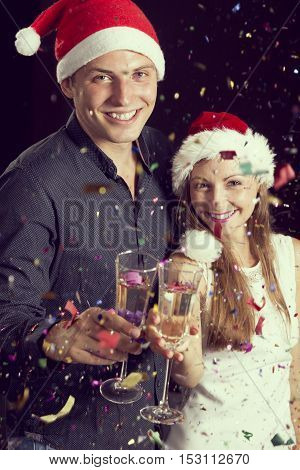 Beautiful young couple in love having fun at a party holding glasses of champagne and making a toast