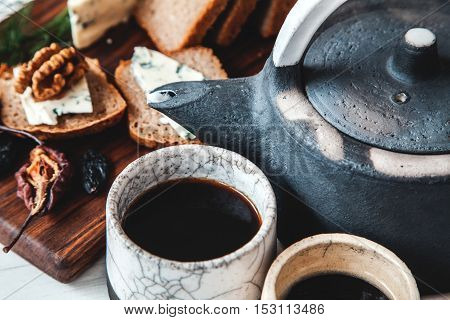 Old Ceramic Teapot With A Cup Of Tea And Biscuits In A Bowl On Wooden Background