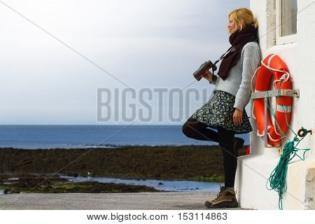 Young Caucasian blonde woman holding binoculars by seaside near a lighthouse with a life buoy