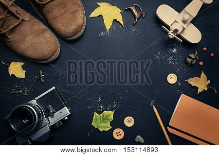 Composition of suede shoes retro camera wooden airplane yellow leaves notebook pencil on a dark scratched background. In the center of the free space for your design. Mock up for art work.