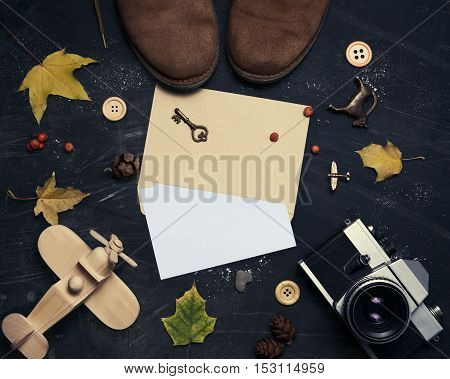 Composition of suede shoes retro camera wooden airplane yellow leaves envelope on a dark scratched background. In the center of the envelope with a blank sheet of paper. Mock up for art work.