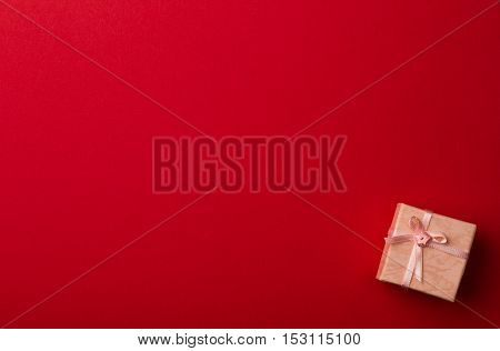 Top view of red background with small pink gift box with white ribbon for greeting cards
