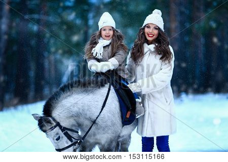 Young beautiful mother with her daughter on a pony winter