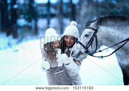 little girl and mom feeding little horse pony winter