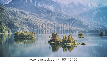 Fantastic sunrise on mountain lake Eibsee, located in the Bavaria, Germany. Dramatic unusual scene. Alps, Europe. Toned like Instagram filter