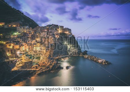 Amazing view of Manarola city at evening light with costal rocks on a foreground. Cinque Terre National Park, Liguria, Italy, Europe. Toned like Instagram filter
