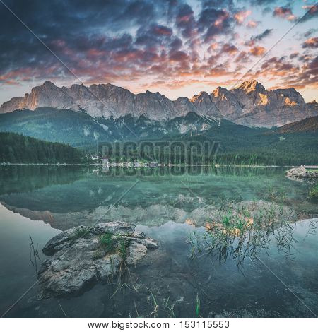 Fantastic sundown on mountain lake Eibsee, located in the Bavaria, Germany. Dramatic unusual scene. Alps, Europe. Toned like Instagram filter