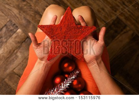 Top view of woman holding Christmas decoration items in her lap and a red textile star in her hands