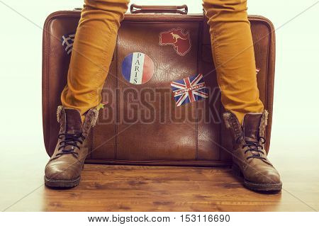 Retro woman in brown shoes standing next to a vintage leather suitcase