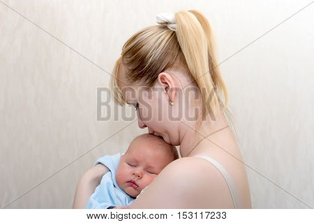 Mom kisses a sleeping baby in her arms close up shot