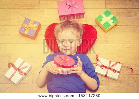 Happy little boy opening presents on holiday, holiday and celebration