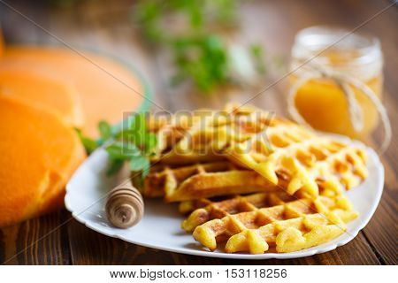 pumpkin waffles with honey on a wooden table