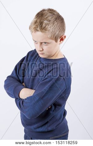 Closeup portrait of displeased, pissed off, angry, grumpy blue eyes boy man with bad attitude, arms crossed looking at you, isolated on white background.