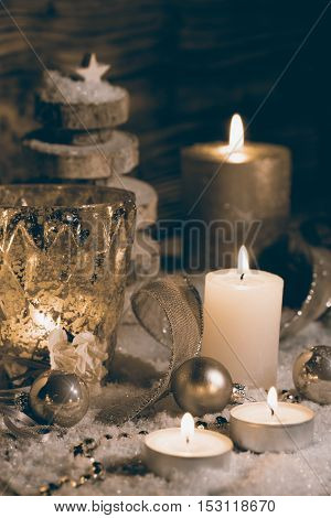 Christmas decoration with candles in snow against dark background