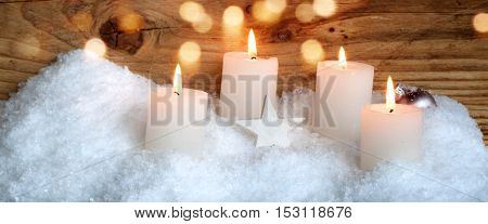 Christmas motif with four advent candles snow and bokeh for a greeting card