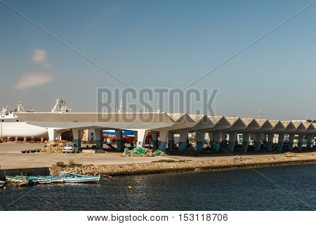 Fishing boats moored to the shore next to the structure. Mahdia, Tunisia.
