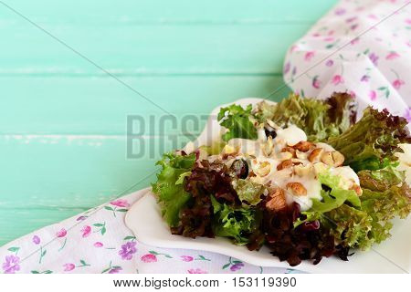 Mixed salad leaves with yogurt and hazelnuts on a plate. Healthy eating. Wooden background. Closeup