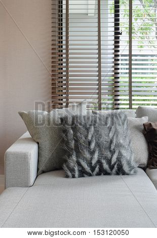 Fluffy Pillows And Earth Tone Pillows Setting On Beige L Shape Sofa