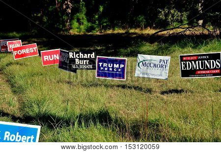 Pittsboro NC - October 23 2016: A row of political advertising campaign signs for both local and national candidates at the intersection of two rural roads