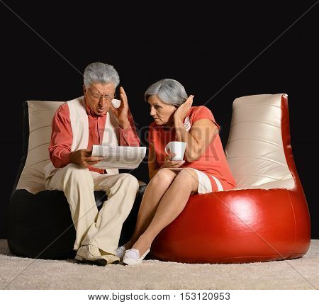 Senior couple reading newspaper with coffee sitting in red armchair on black background