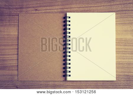 top view of opened sketch book with blank area for message on wood table