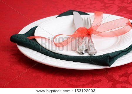 closeup of christmas place settings on red tablecloth