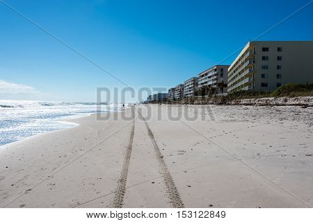 Tire tracks left in the sand on a coastal beach with buildings