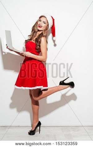 Full length portrait of a young excited woman in red santa claus dress and hat standing and holding laptop isolated on the white background