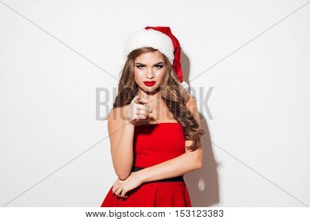 Concentrated brunette woman in red santa claus dress and hat looking at camera and pointing finger isolated over white background