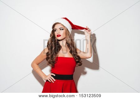 Beautiful young brunette woman in red dress and hat posing isolated over white background