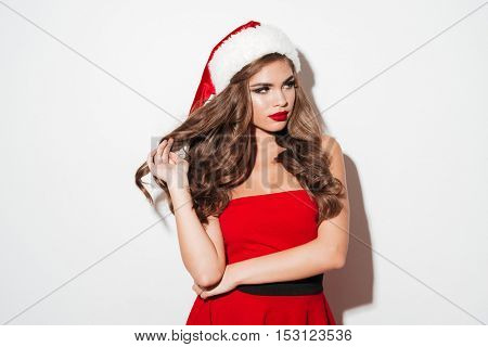 Portrait of a beautiful sexy brunette woman in red christmas dress looking away isolated over white background