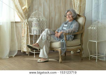 Portrait of beautiful elderly woman on chair in vintage room