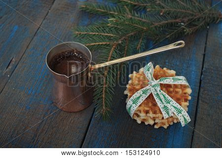 hot brewed coffee with Crema in the Turk and waffles on blue wooden background