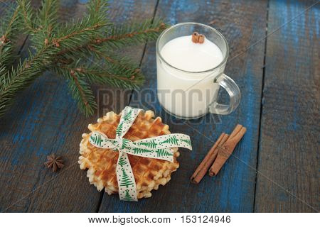 milk with cinnamon in a transparent mug, waffles, cakes, tied with Christmas ribbon, anise on blue wooden background