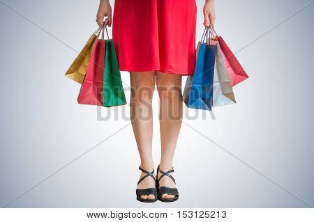 Legs Of Shopping Woman Holding Many Colorful Bags In Hands.