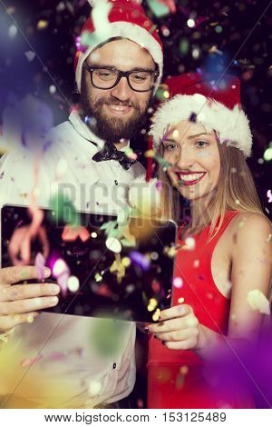 Young couple in love having fun at New Year's Eve party and taking a midnight selfie