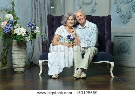 Portrait of beautiful elderly couple in vintage interior with flowers