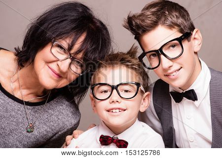 Beautiful grandmother posing with her grandchilds. Fashionable young boys smiling. Family portrait. Happiness.