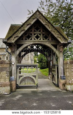 Beautiful elaborate carved stone and wood lychgate entrance to English village Church