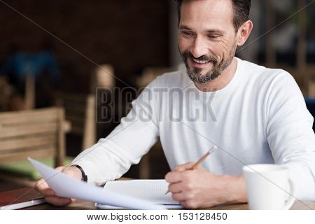 Work brings satisfaction. Smiling bearded man holding some papers and taking notes while sitting in cafe.
