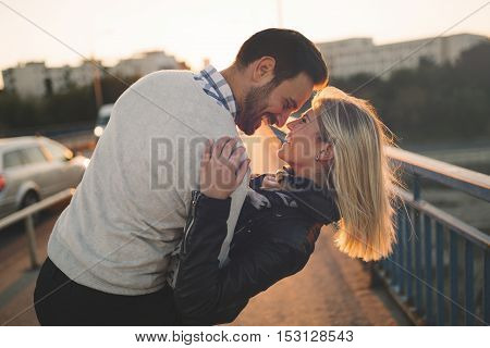Romantic couple in love enjoying sunset and kissing