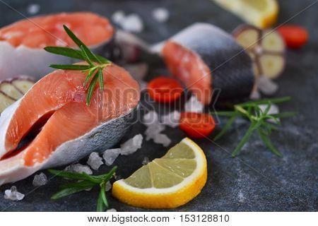 Fresh raw salmon steak with lemon and salt on black marble background