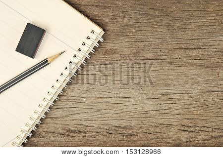 Education topic. Close up of notebook with pencil and eraser on top