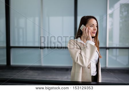 Serious businesswoman using phone at the offices
