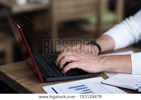 Working hard. Close up picture of male worker typing on modern laptop.