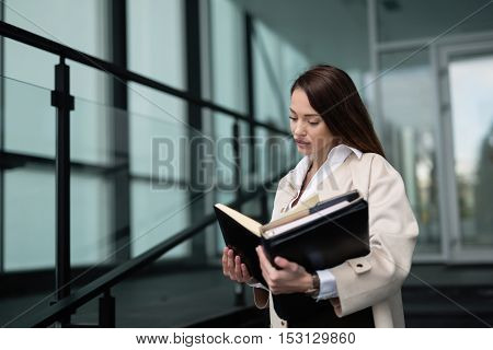Beautiful young businesswoman reading in modern office