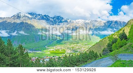 The forests of Kazbegi National Park with Stepantsminda resort in sunny valley Georgia.