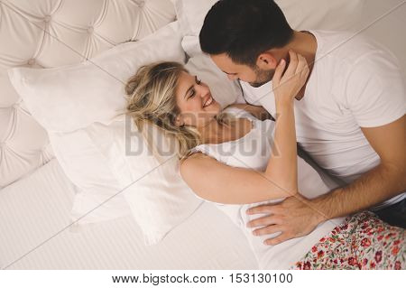 Passionate young beautiful couple foreplay in bed