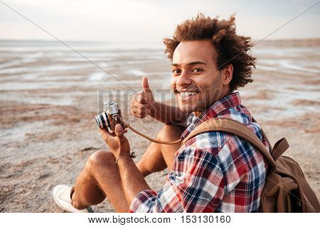 Happy african american young man with backpack taking photos and showing thumbs up on the beach